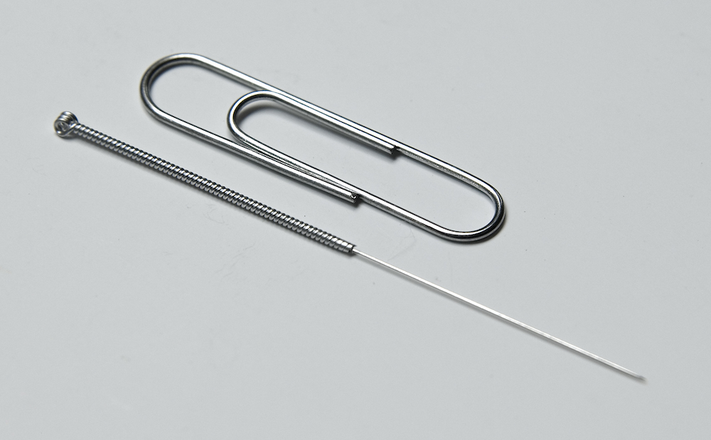 An acpuncture needle is as thin as two human hairs, or 25% of the width of a paperclip